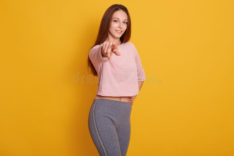 Portrait of young Caucasian athletic girl pointing at camera, looking smiling at camera, wearing stylish sporty clothing, model royalty free stock photos