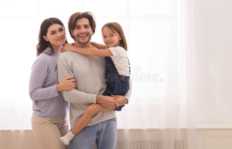 Portrait of young caucasian family with little daughter on hands royalty free stock photography