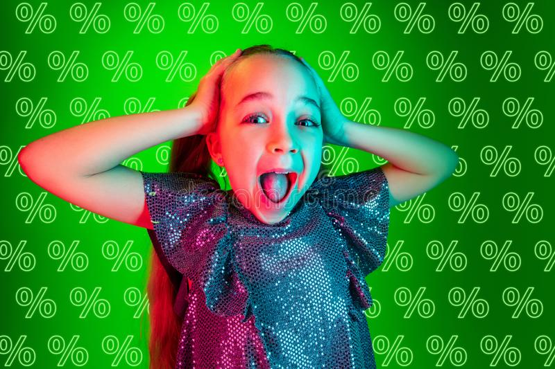 Portrait of little girl on green background, black friday. Portrait of young caucasian girl on green background with neon percents. Shocked, crazy happy royalty free stock images