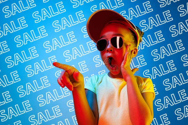Portrait of little girl on blue background, black friday. Portrait of young caucasian girl in sunglasses on blue background with neon lettering. Concept of sales royalty free stock photography