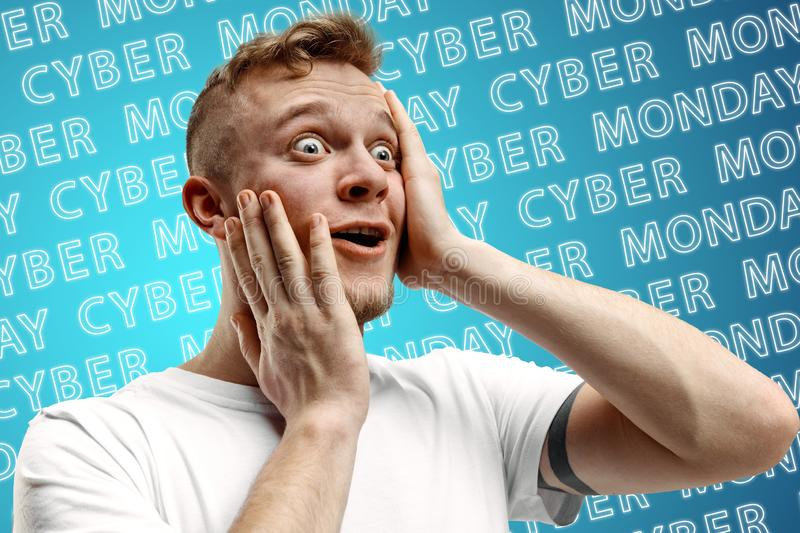 Portrait of young man on blue background, black friday. Portrait of young caucasian man on blue background with neon lettering. Shocked, astonished. Concept of stock image