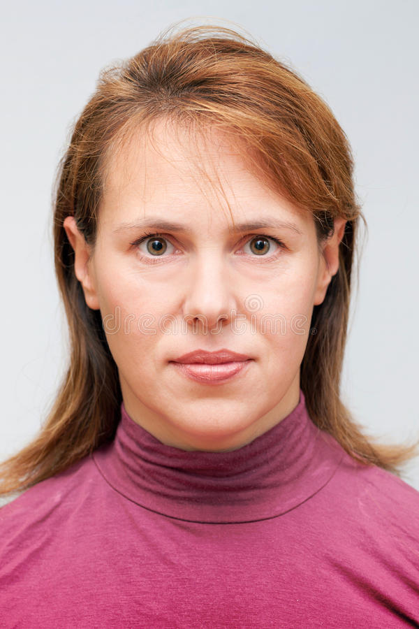 Portrait of young Caucasian ordinary woman. Closeup studio face portrait of young Caucasian ordinary woman on gray background stock photo