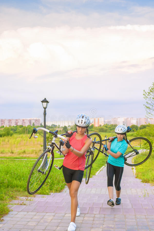 Portrait of Young Caucasian Sportswomen Work Out with Bicycle Outside stock photos
