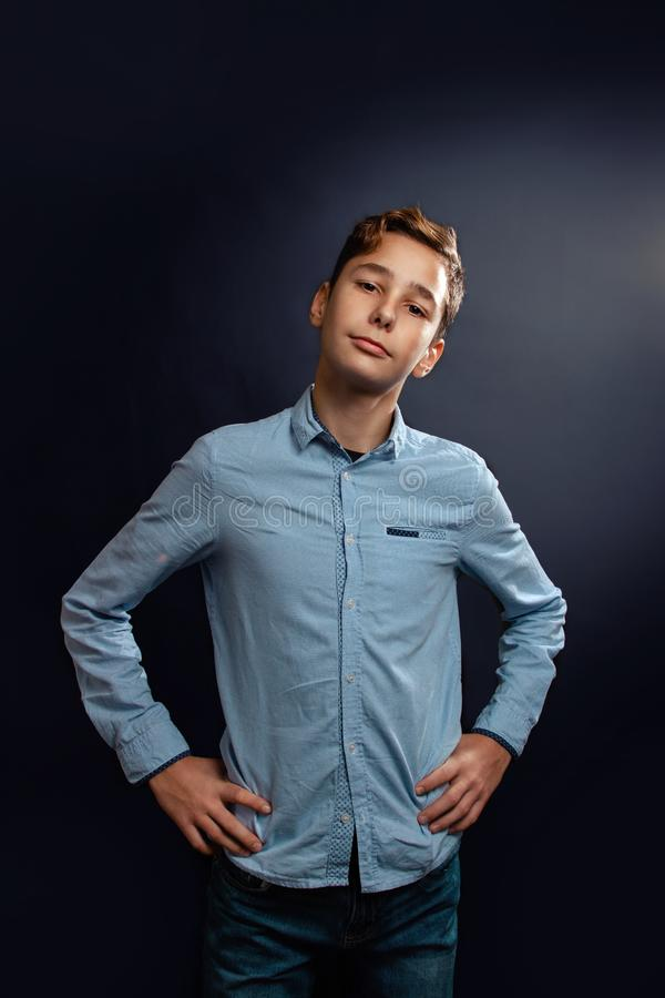 Portrait of a young caucasian teenage boy in a shirt. Black background stock photography