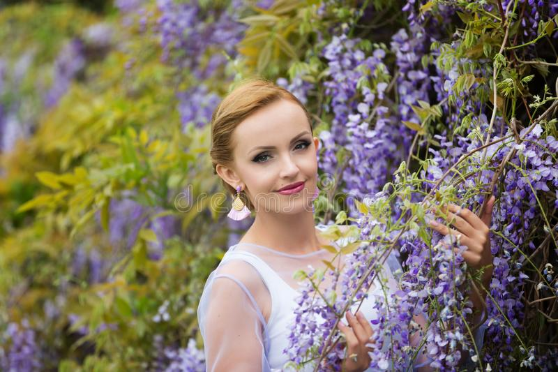 A portrait of young Caucasian woman with blond hair near purple wisteria, looking straight to camera. royalty free stock images