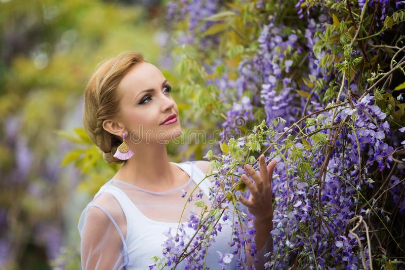 Two woman hands holding wisteria blooming vineA portrait of young Caucasian woman with blond hair near purple wisteria, looking up stock photos