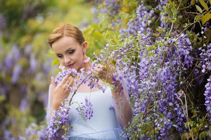 Two woman hands holding wisteria blooming vineA portrait of young Caucasian woman with blond hair near purple wisteria, looking up stock images