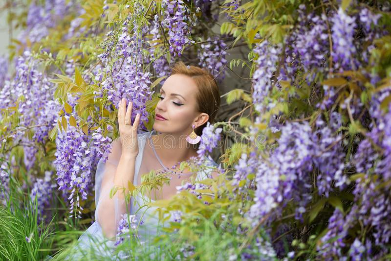Portrait of young Caucasian woman with blond hair near purple wisteria,smelling the blooms, enjoying wisteria, eyes closed royalty free stock photography