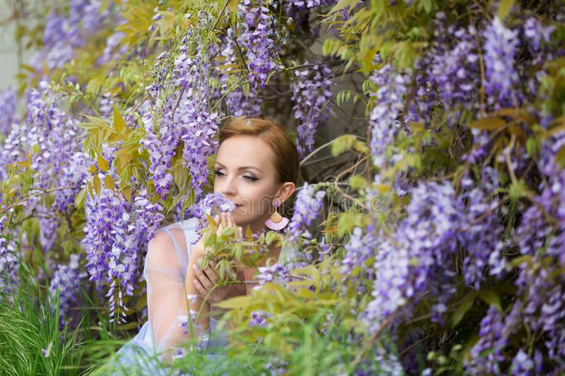 Portrait of young Caucasian woman with blond hair near purple wisteria,smelling the blooms, enjoying wisteria, eyes closed royalty free stock photo