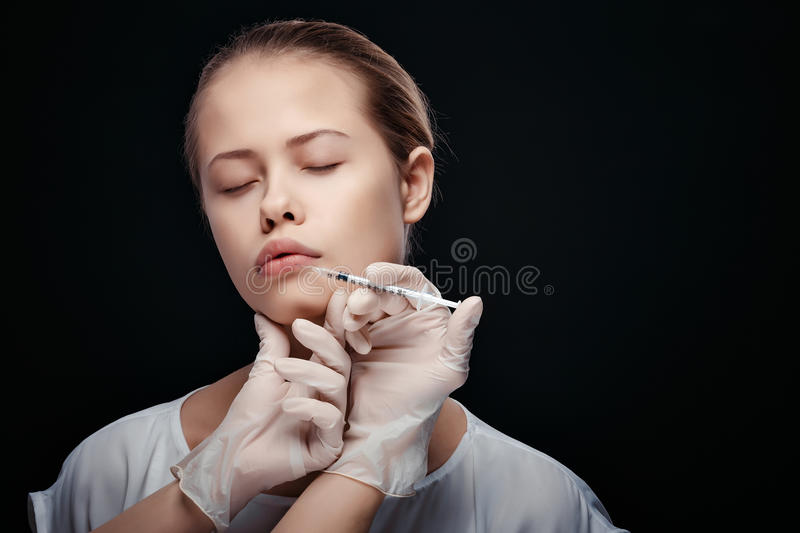 Portrait of young Caucasian woman getting cosmetic injection royalty free stock photos