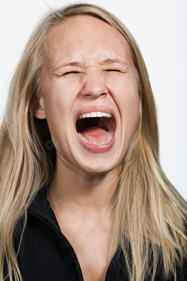 Portrait of young Caucasian woman screaming stock photo