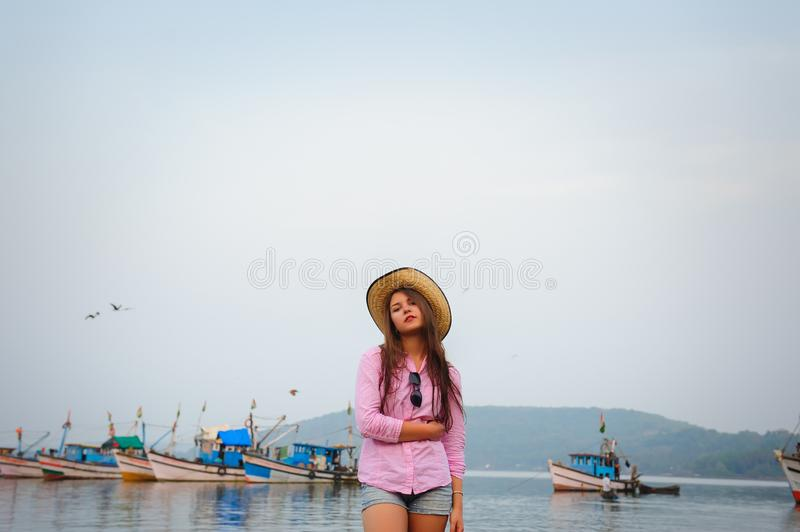 Portrait of young caucasian woman in straw hat and short denim shorts on a warm cloudy day. Beautiful long-haired brunette stock image