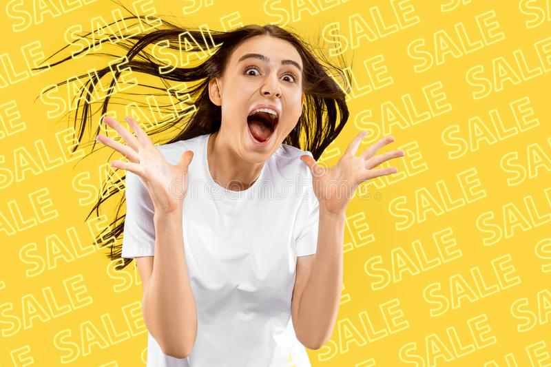 Portrait of young woman on yellow background, black friday. Portrait of young caucasian woman on yellow background. Screaming, shocked, wondered, astonished royalty free stock photos