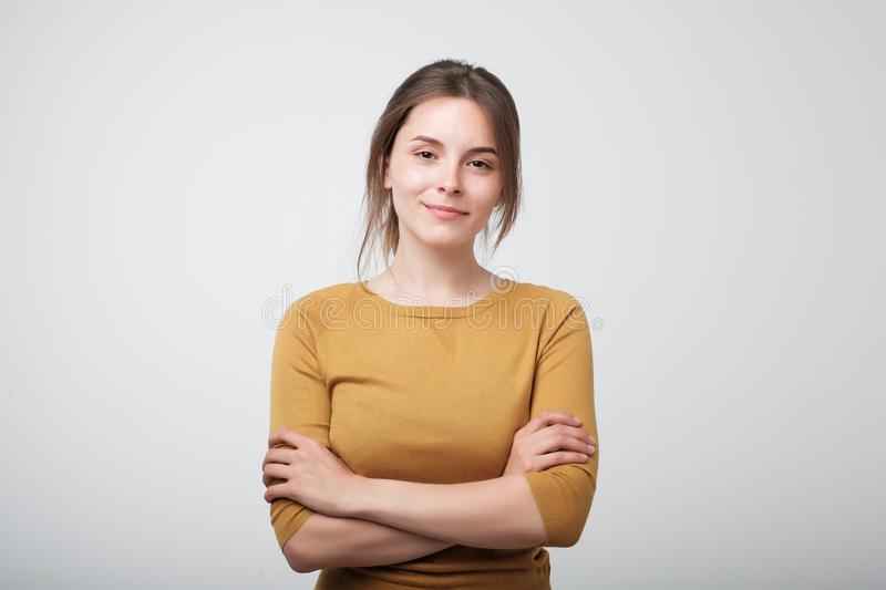 Portrait of young caucasian woman in yellow shirt casually standing near gray wall royalty free stock photography