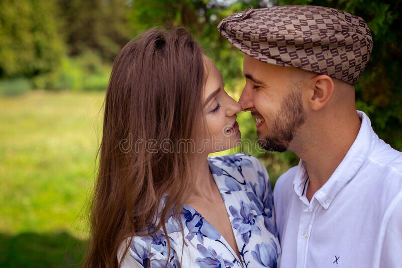 Portrait of young charming couple in love touch their noses and smiles at the green park stock image