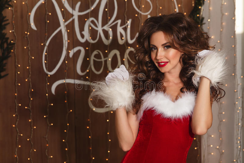 Portrait of a young charming girl dressed as Santa. Happy New Year! royalty free stock photos