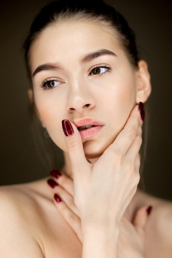 Portrait of young charming girl with natural makeup holding her hands on her face stock photo