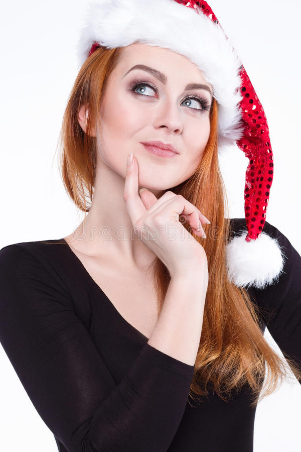 Portrait of a young charming red-haired girl in a shiny Christmas hat. stock photos