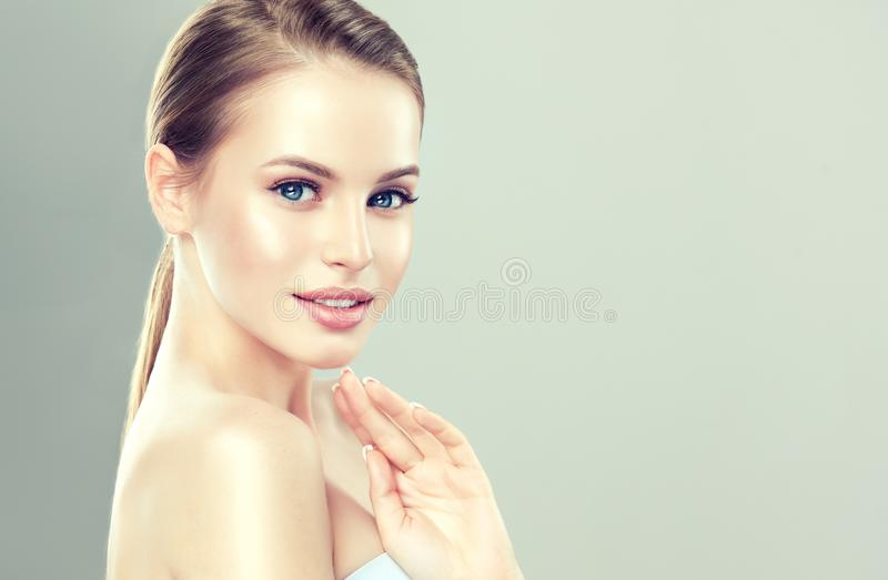 Portrait of young, charming woman with hairstyle gathered in the bunch. Model with clean fresh skin and soft, delicate make up. stock photo