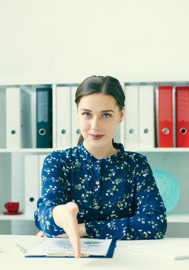 Portrait of young cheerful beautiful business woman giving hand for handshake. royalty free stock image