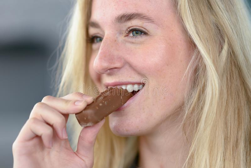 Cheerful blond woman eating chocolate royalty free stock photos