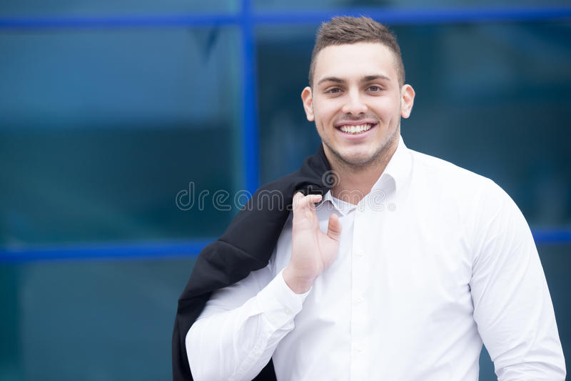 Portrait of young cheerful businessman smiling at camera stock images