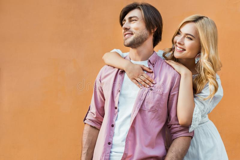 portrait of young cheerful couple looking away while standing against city royalty free stock photography
