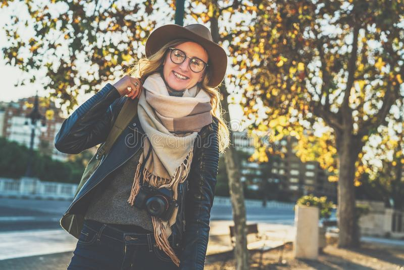Portrait of young cheerful woman tourist in hat, glasses and with backpack and camera. Girl is standing on city street. royalty free stock images