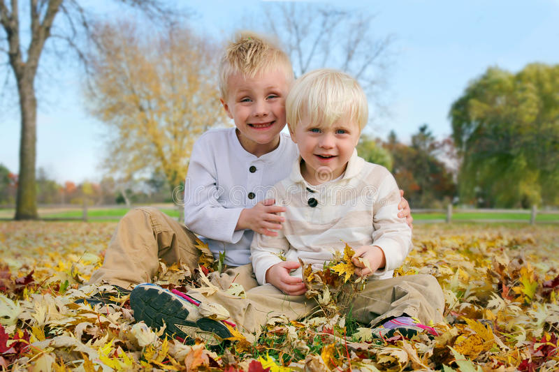 Portrait Young Children Outside in Fallen Autumn Leaves stock images