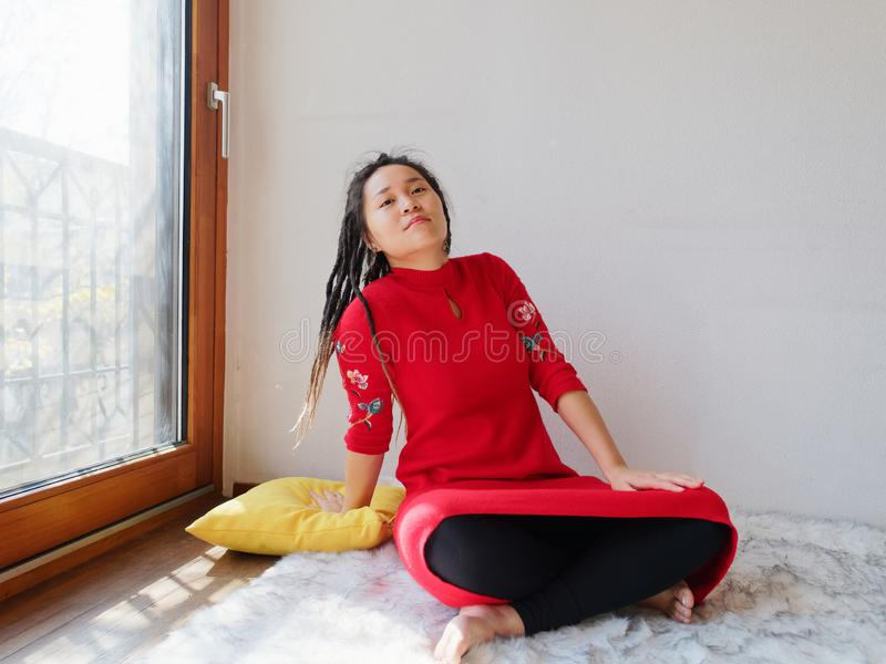 Portrait of young Chinese female with cute dreadlocks in sunny home isolated with white wall background, sitting on furry carpet stock photo