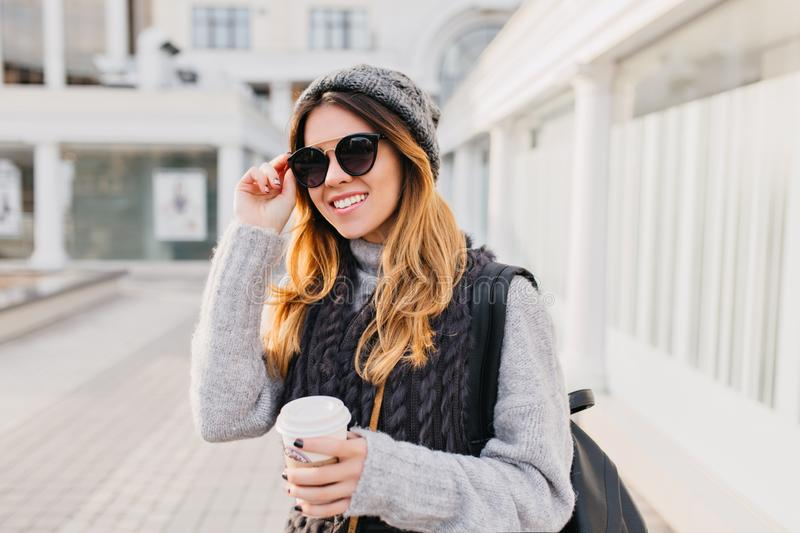 Portrait young city fashionable woman in modern sunglasses, warm woolen sweater, knitted hat smiling on street. Cheerful stock photos