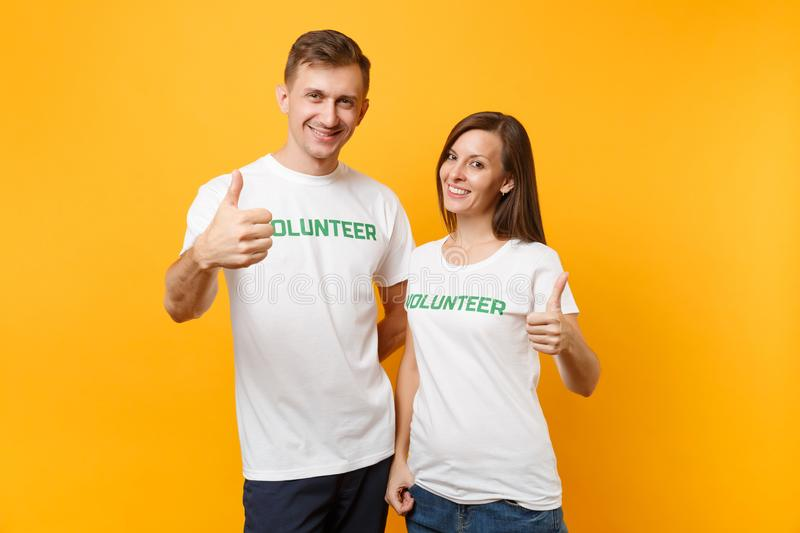 Portrait of young colleagues couple in white t-shirt with written inscription green title volunteer isolated on yellow royalty free stock photography