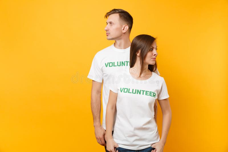 Portrait of young colleagues couple in white t-shirt with written inscription green title volunteer isolated on yellow royalty free stock images