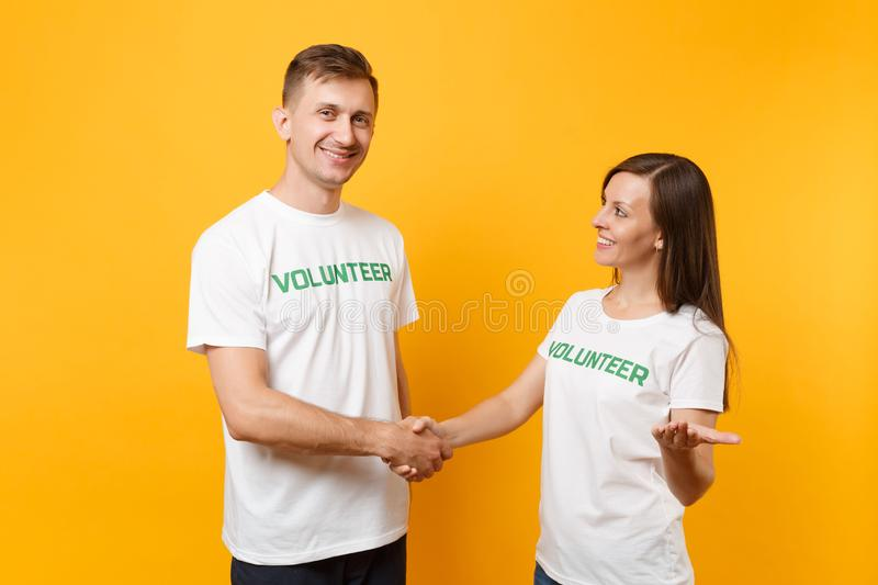 Portrait of young colleagues couple in white t-shirt with written inscription green title volunteer isolated on yellow stock photo