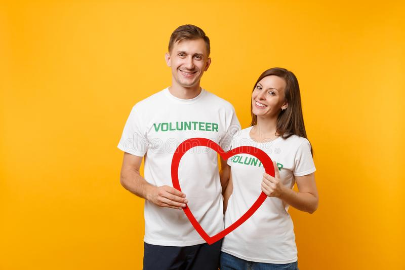 Portrait of young colleagues couple in white t-shirt with written inscription green title volunteer isolated on yellow royalty free stock photos