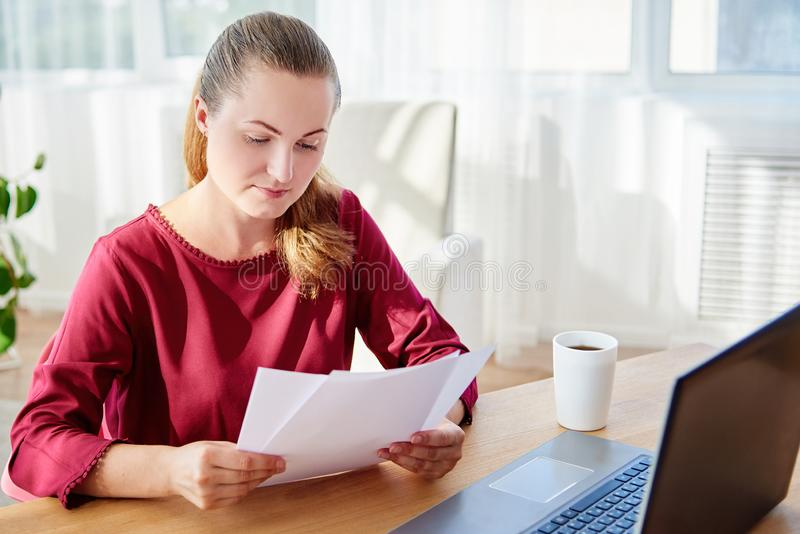 Portrait of young confident business woman sitting at wood desk with laptop and reading documents in modern office, copy space stock photos