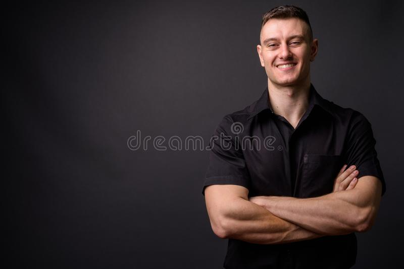 Portrait of young confident businessman smiling with arms crossed looking at camera royalty free stock photography