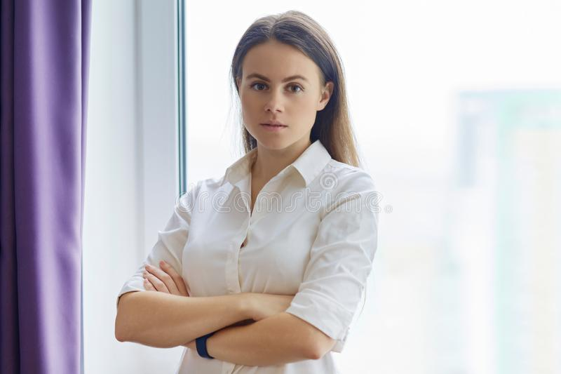 Portrait of young confident businesswoman with arms crossed near office window, female looking into camera smiling royalty free stock photos