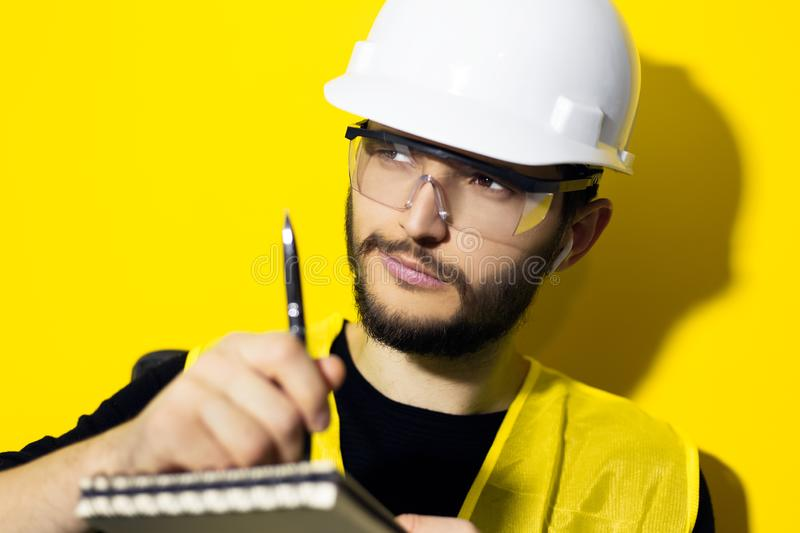 Portrait of young confident man, builder engineer writing in notebook, wearing safety helmet and glasses for construction, isolate. D on yellow background stock image