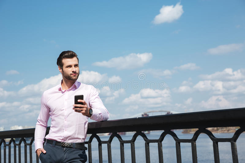 Portrait of young confident man using smartphone near river stock images