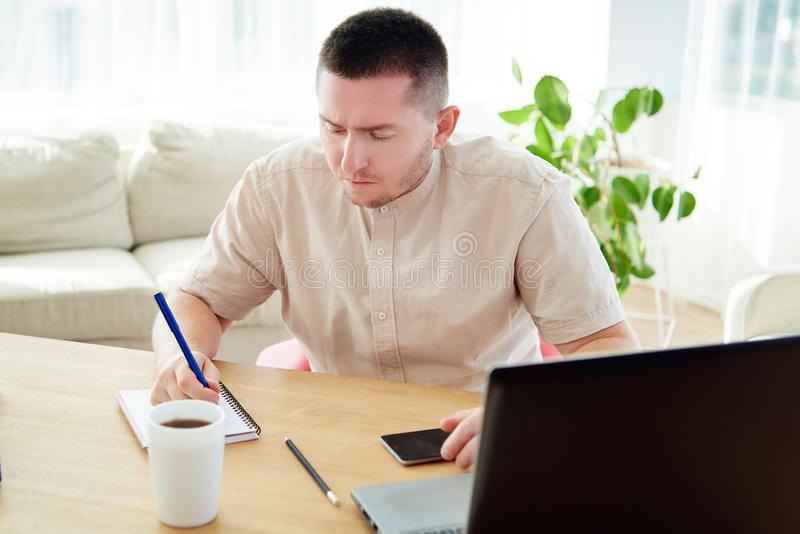 Portrait of young confident manager making notes and working on laptop computer, copy space. Handsome businessman sitting at wood stock image