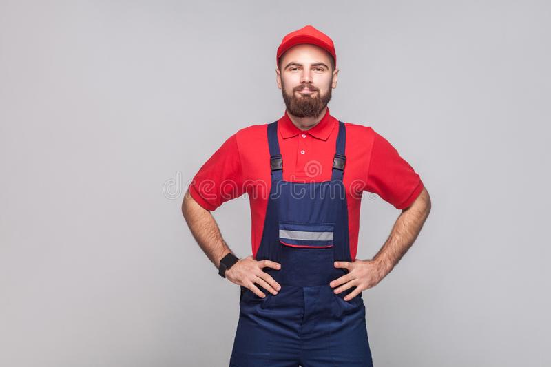 Portrait of young confident repairman with beard in blue overall stock photos