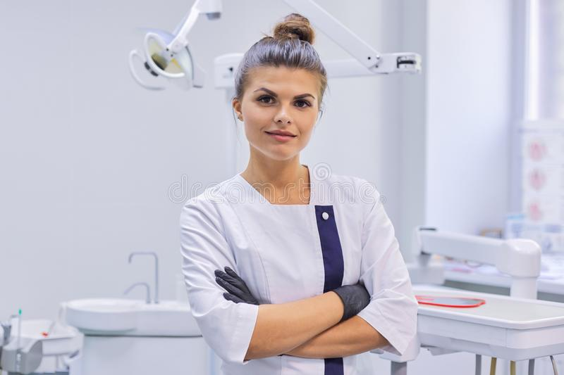 Portrait of young confident smiling dentist doctor woman, female with arms crossed royalty free stock photo