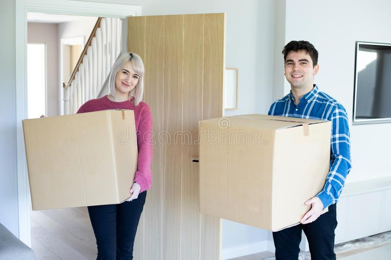 Portrait Of Young Couple Carrying Boxes Into New Home On Moving Day stock photography