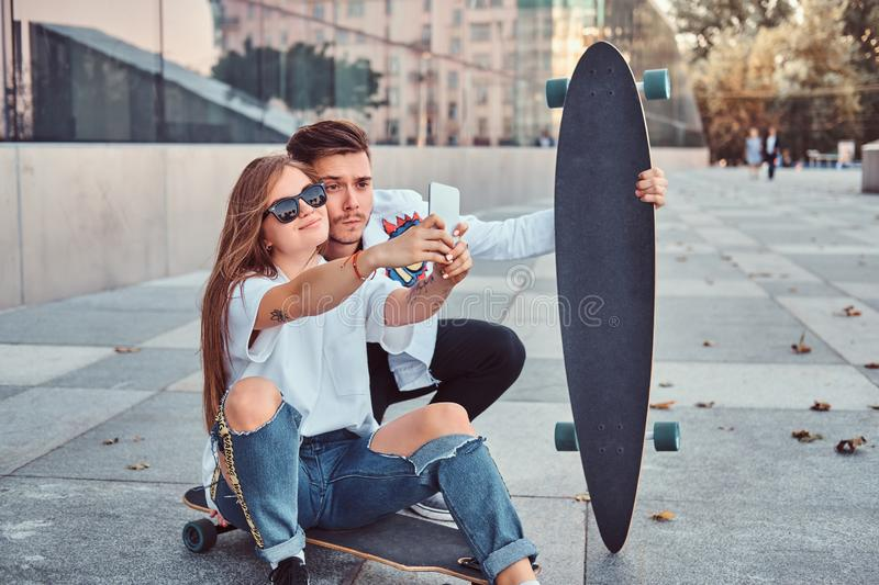 Portrait of young couple dressed in trendy clothes having fun while makes a selfie together outdoors. Portrait of a young couple dressed in trendy clothes royalty free stock photos