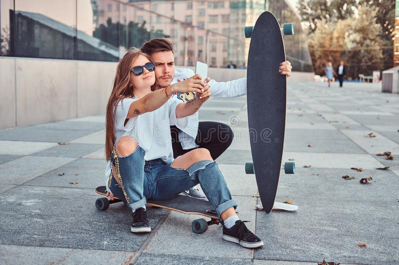 Portrait of young couple dressed in trendy clothes having fun while makes a selfie together outdoors. Portrait of a young couple dressed in trendy clothes stock photos