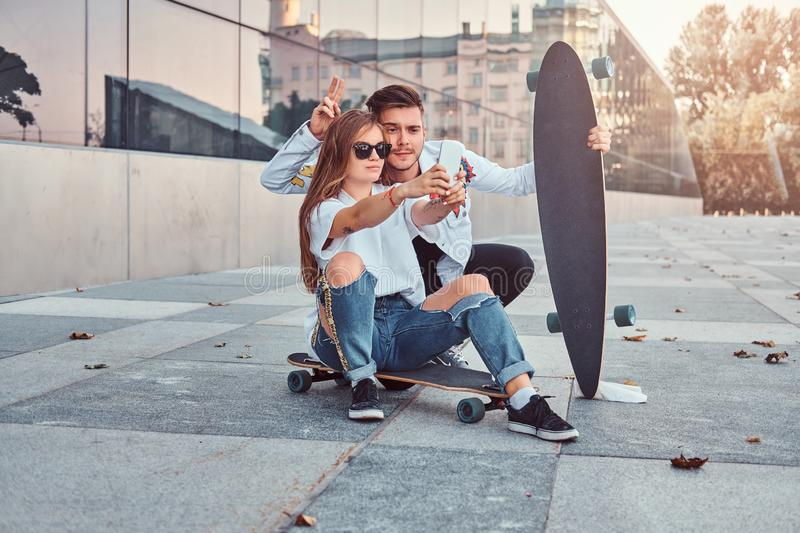 Portrait of young couple dressed in trendy clothes having fun while makes a selfie together outdoors. Portrait of a young couple dressed in trendy clothes stock photo