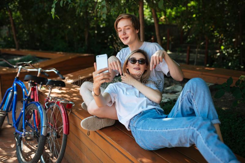 Young couple having fun in park with bicycles nearby. Boy sitting on bench in park with nice girl with blond hair that stock photos