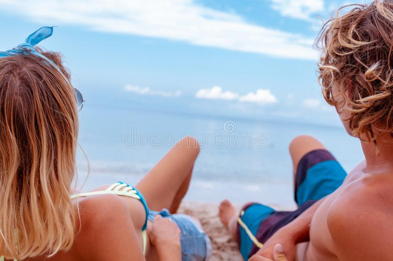 Portrait of young couple in love at beach and enjoying time being together. Young couple having fun on a sandy coast. Portrait of young couple in love at beach royalty free stock photo