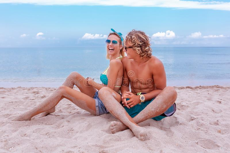 Portrait of young couple in love at beach and enjoying time being together. Young couple having fun on a sandy coast. Portrait of young couple in love at beach royalty free stock photos